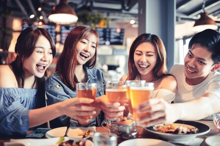 happy young group dining and drinking beer at restaurant