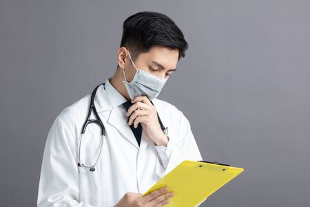 young Doctor Wear Medical Mask looking at exam report 版權商用圖片