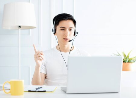 smiling young man working from home with laptop