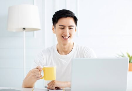 young man working at home with laptop