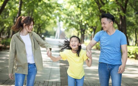 Young asian family with child having fun in nature park Stock Photo