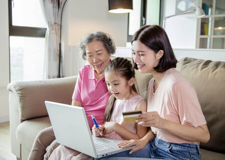 Happy grandmother with little kid and daughter having fun online shopping  at home  Stock Photo