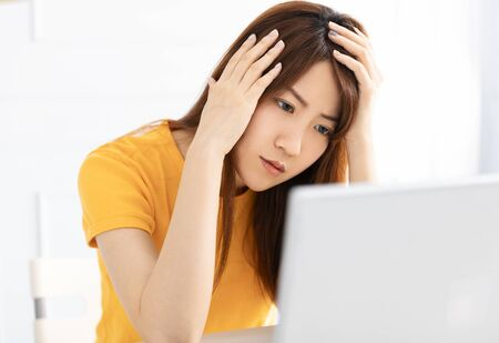 stressed young using laptop at home