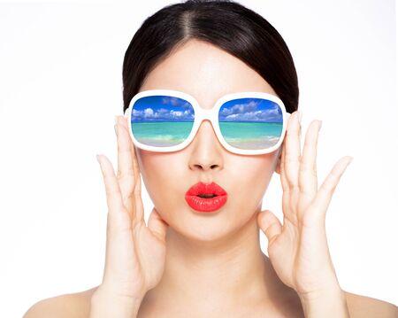 Jeune beauté en gros plan dans des lunettes de soleil avec réflexion sur la plage Banque d'images
