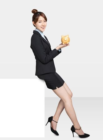 young Business woman sitting on blank billboard and showing the piggy bank