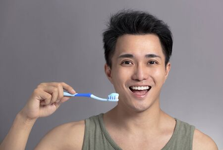 smiling asian young man with toothbrush . health and beauty concept