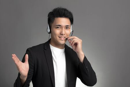 Smiling young asian businessman talking on headset against gray background
