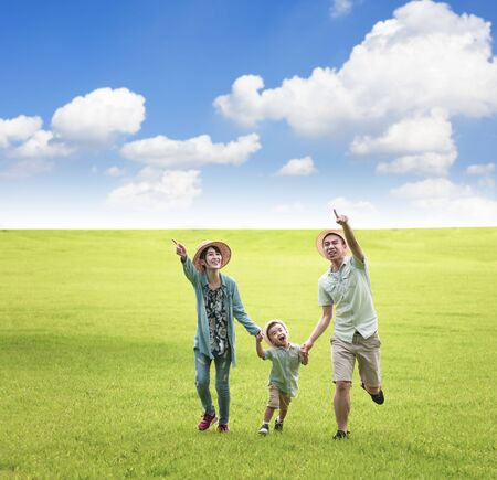 Happy family running together on the grass