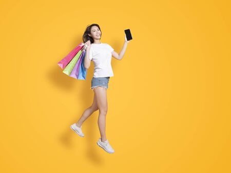 happy young woman holding shopping bags and showing the phone