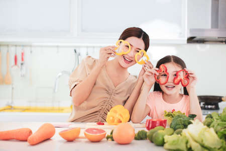 happy Mother and child daughter preparing the vegetables and fruit in kitchen
