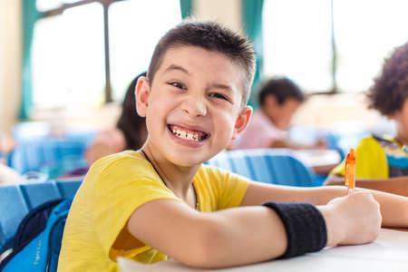 naughty school boy looking the camrea in classroom Banco de Imagens