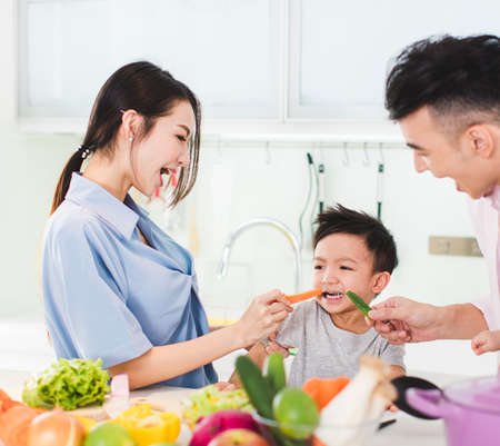 parent feeding boy a piece of carrot in kitchen