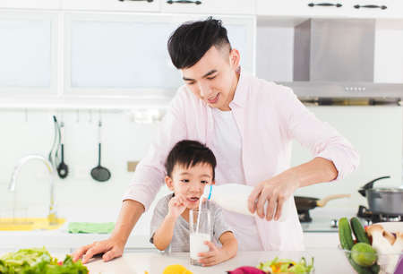 Father and son having breakfast with milk at kitchen
