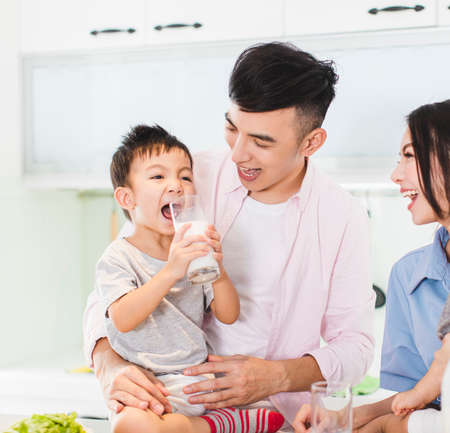 Happy family having breakfast with milk at kitchen