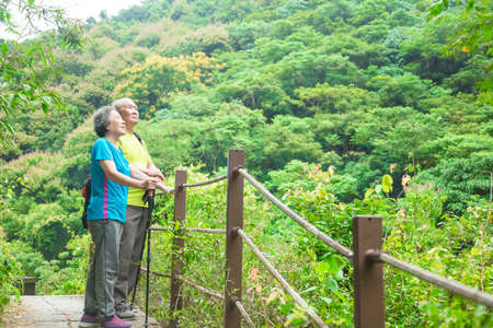 Happy Asian senior couple hiking in nature park 스톡 콘텐츠