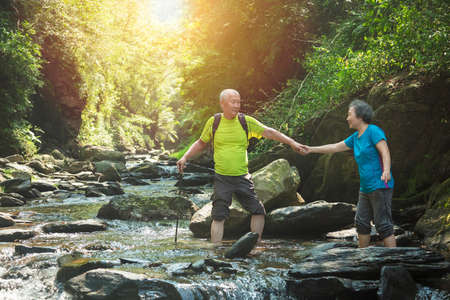 Senior couple walking across small river in nature park