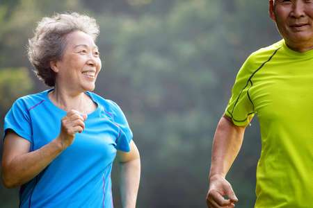 Asian Senior Couple jogging in the nature park