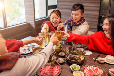 happy young group toasting beer at hot pot restaurant Stock Photo