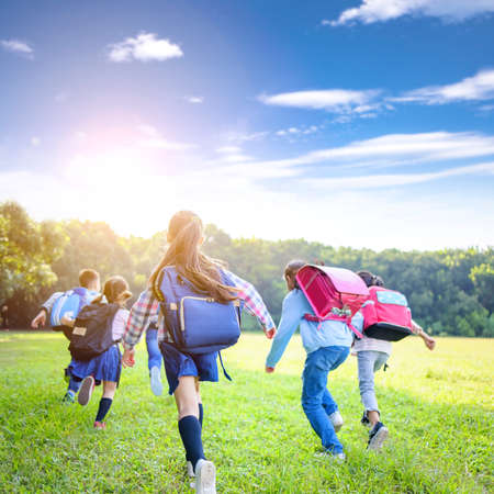 rear view of elementary school kids running on the grass