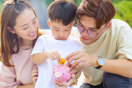 happy parent holding piggy bank and teaching son save money