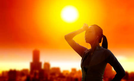 Woman shielding her eyes from sun with summer heat wave in the city background
