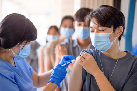 Doctor injecting vaccine for students in high school