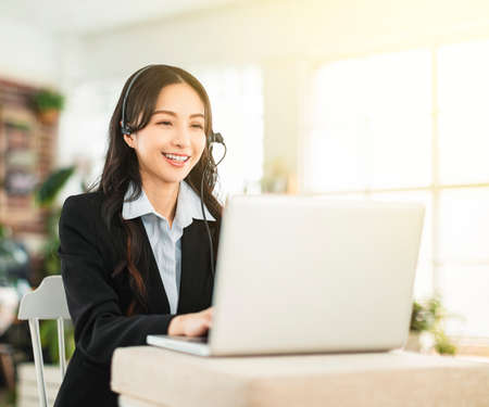 Business woman in headphone and working in home office Banco de Imagens