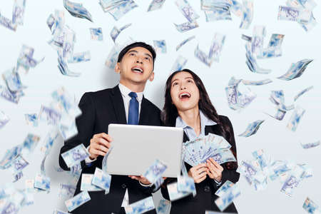 Excited young business man and woman under the money rain