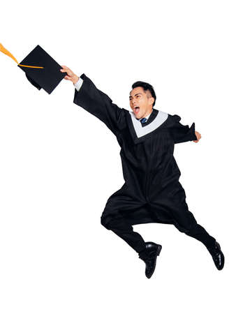 Excited young man in black graduation gown and cap holding a diploma