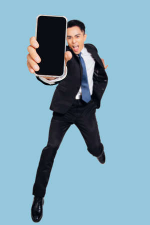 Excited Young business man dancing and showing the mobile phone screen
