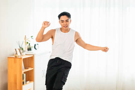 Happy Asian young man Doing Exercises at Home