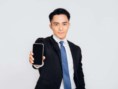 Young business man showing the mobile phone screen