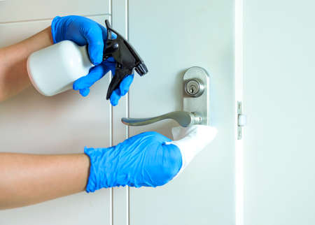 Cleaning door handles with an antiseptic Stok Fotoğraf