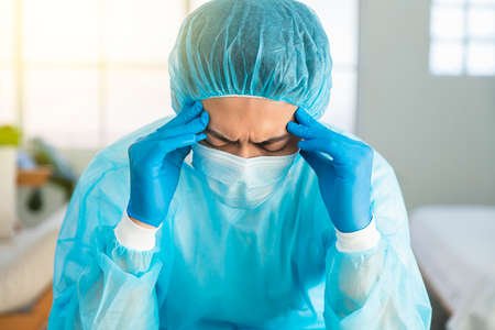 Doctor wear face mask, gloves, blue green uniform showing heart hands shape and stay home concepts Stok Fotoğraf