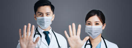 Doctor in face mask and showing stop sign with hands