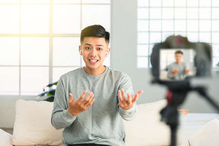 Young man recording video for an internet tv show or tutorial streaming