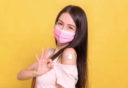 Happy young woman wearing medical mask and showing her arm with ok gesture after getting vaccine.