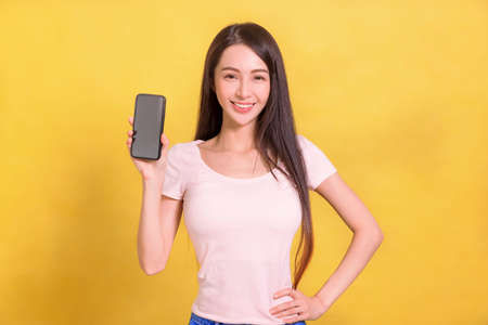 Beautiful young woman showing blank screen of mobile phone.
