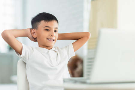 Boy looking at laptop.Relaxing and watch video.Study online.