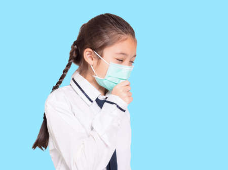 Girl in a medical mask coughing.Isolated on blue background. Фото со стока