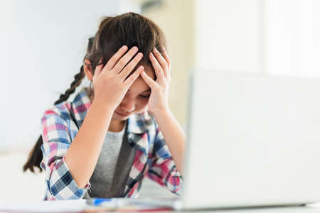 Frustrated student girl study online on laptop at home.