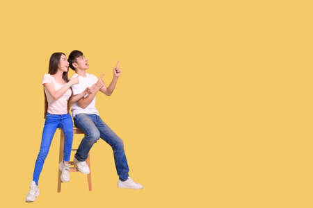 happy excited Asian couple pointing hands to empty space