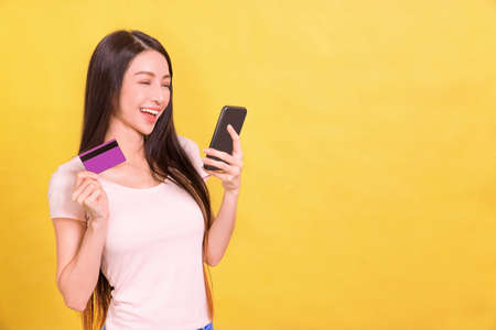 Happy young woman watching the mobile phone and showing credit card.