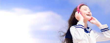 Happy Teenager student girl enjoy listen music with headphone Фото со стока
