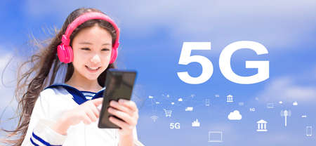 Happy syudent girl listening music in headphones and holding mobile phone with 5G network concepts