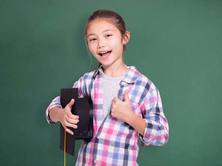 Happy student girl holding graduation cap and showing thumb up.Isolated on green chalkboard background.