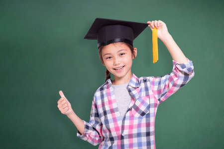 Happy student girl wearing graduation cap and showing thumb up.Isolated on green chalkboard background.