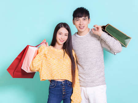 Happy couple with shopping bags.Isolated on blue background.