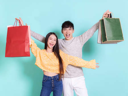 Excited young couple holding shopping bags.Isolated on blue background.
