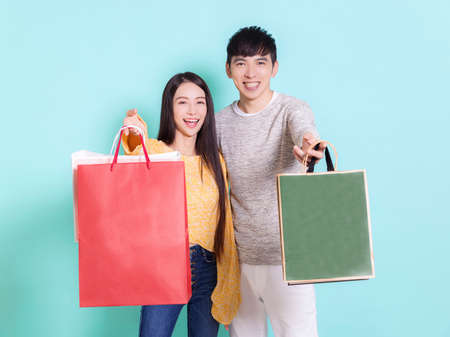Happy couple showing shopping bags.Isolated on blue background. Фото со стока